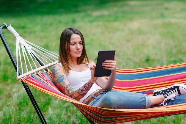 Mujer joven con tableta en la hamaca