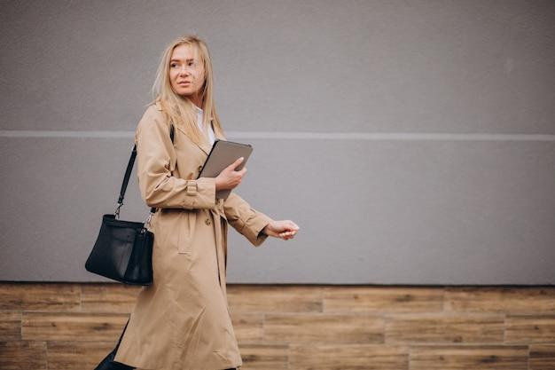 Mujer joven con tableta por la pared exterior de la calle