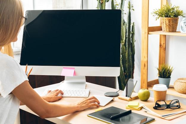 Mujer joven y tableta que trabajan en la oficina en casa.