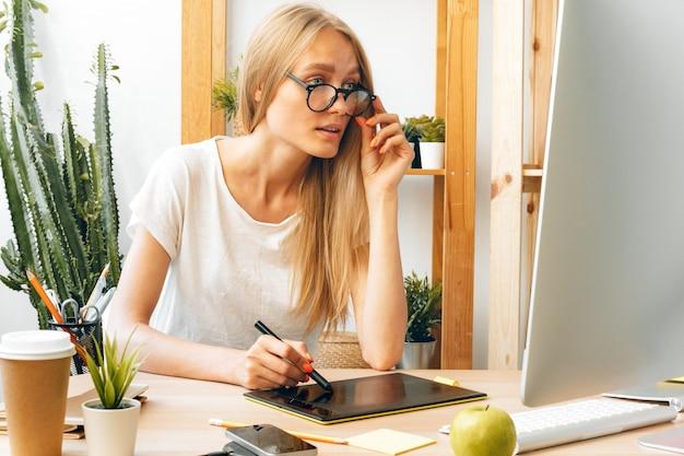 Mujer joven y tableta trabajando en la oficina en casa