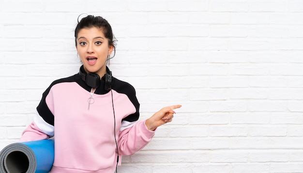Mujer joven con tapete sobre pared de ladrillo blanco sorprendida y apuntando el dedo hacia el lado