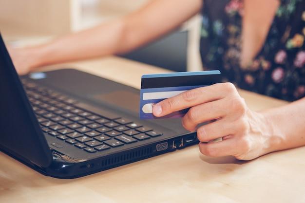 Mujer joven con tarjeta de crédito está comprando en línea en la oficina