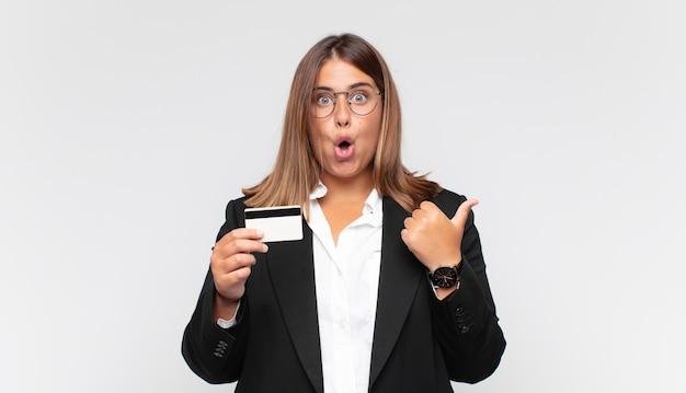 Mujer joven con una tarjeta de crédito mirando asombrada con incredulidad, apuntando a un objeto en el costado y diciendo wow, increíble