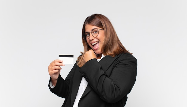 Mujer joven con una tarjeta de crédito que se siente feliz, positiva y exitosa, motivada al enfrentar un desafío o celebrar buenos resultados