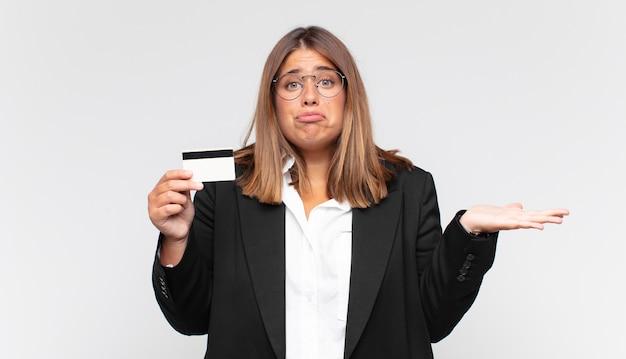 Mujer joven con una tarjeta de crédito que se siente perpleja y confundida, dudando, ponderando o eligiendo diferentes opciones con expresión divertida