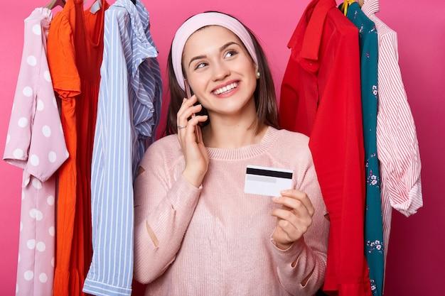 La mujer joven con tarjeta de crédito sueña con ir de compras mientras está parado cerca de lotes perchas con ropa colorida aislada sobre fondo rosa. a fashoin le gustan las compras en línea. niña sonriente compra vestido.