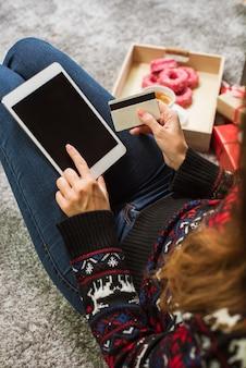 Mujer joven con tarjeta de crédito y tableta en navidad