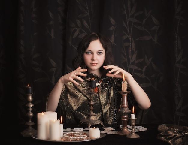 Mujer joven con tarjetas de adivinación en la habitación