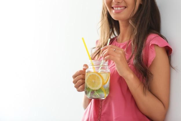 Mujer joven con tarro de masón de limonada fresca a la luz
