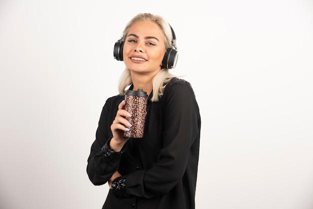 Mujer joven con taza en auriculares sobre un fondo rojo. foto de alta calidad