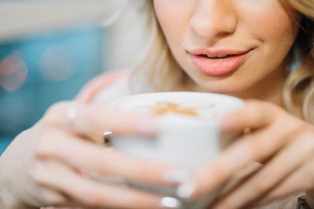 Mujer joven con taza de bebida cerca de la cara