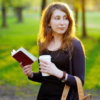 Mujer joven con una taza de café y un libro en el parque al atardecer