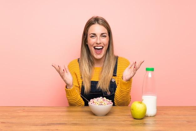 Mujer joven con tazón de cereales infeliz y frustrado con algo