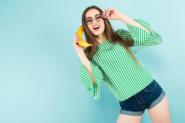 Mujer joven con teléfono banana