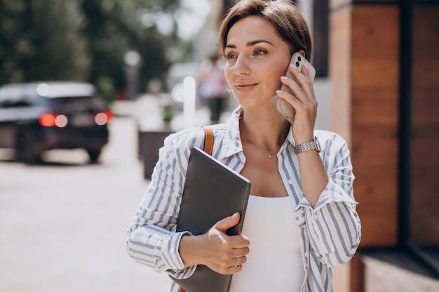 Mujer joven con teléfono y computadora caminando fuera de la calle