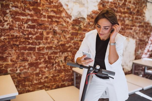 Mujer joven con teléfono y conduciendo en scotter