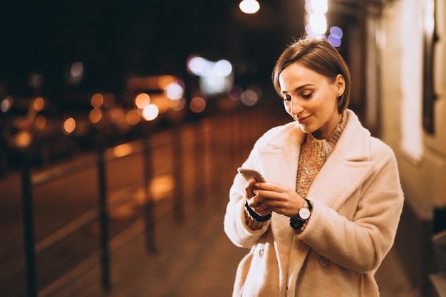 Mujer joven con teléfono fuera de la calle de noche