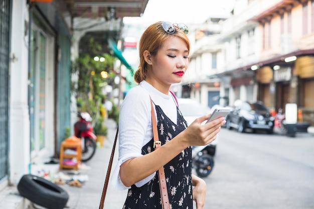 Mujer joven con teléfono inteligente en la calle