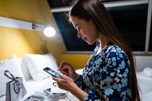 Mujer joven con teléfono inteligente celular. feliz niña hermosa sonriente en la cama en el dormitorio escribiendo en el teléfono inteligente móvil