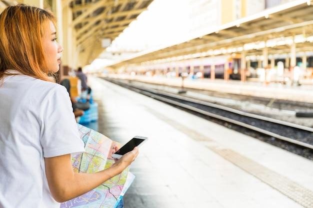 Mujer joven con teléfono inteligente y mapa