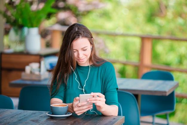 Mujer joven con teléfono inteligente mientras está sentada sola en una cafetería durante el tiempo libre