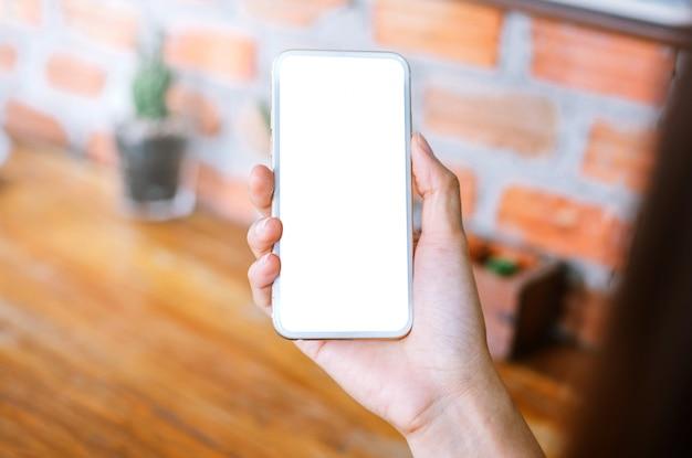Mujer joven con teléfono inteligente con pantalla en blanco mientras está sentado en la sala de estar.