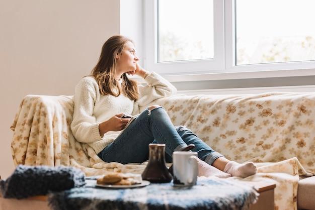 Mujer joven con teléfono inteligente en el sofá junto a la mesa con bebida y galletas