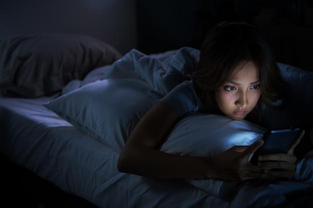 Mujer joven con un teléfono inteligente en su cama por la noche