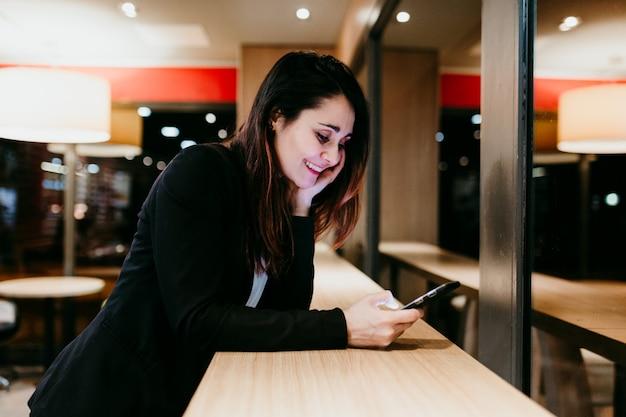 Mujer joven con teléfono móvil en un café o restaurante en el interior. tecnología y estilo de vida