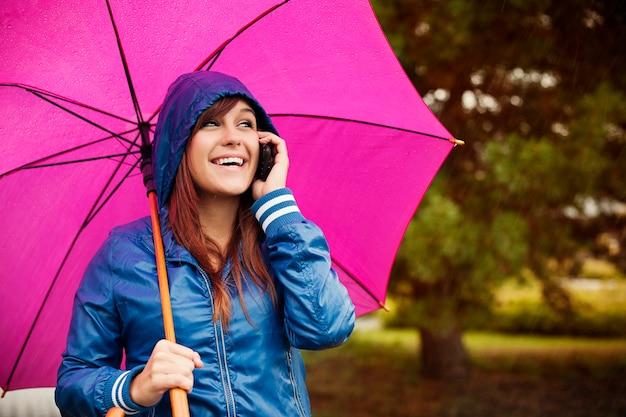 Mujer joven con teléfono móvil en día lluvioso