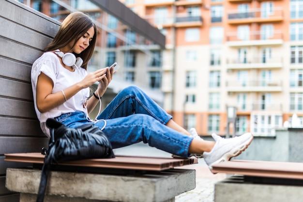 Mujer joven con teléfono móvil escucha música mientras está sentado en el banco en un parque