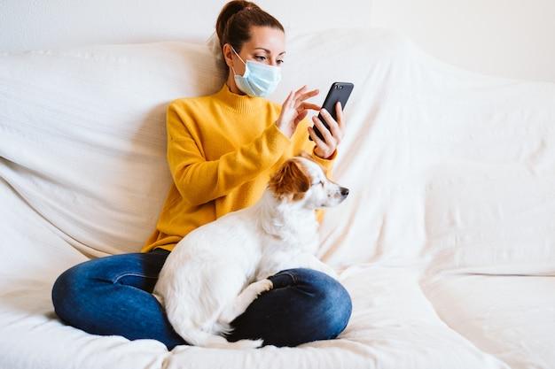 Mujer joven con teléfono móvil, lindo perro pequeño además. sentada en el sofá, con una máscara protectora. concepto de quedarse en casa durante el coronavirus covid-2019