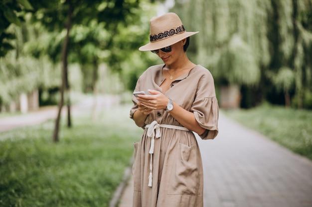 Mujer joven con teléfono móvil en el parque