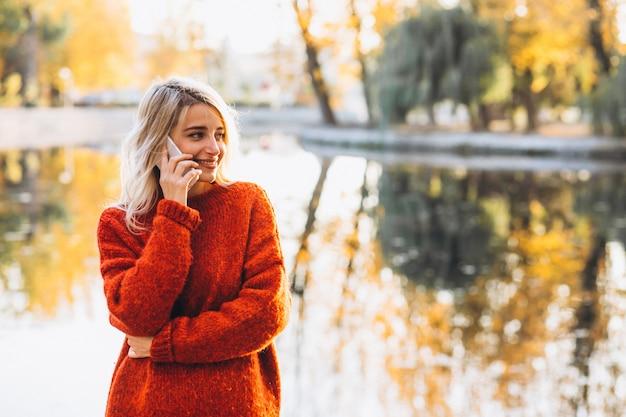 Mujer joven con teléfono en el parque junto al lago