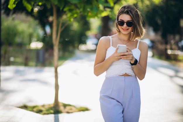 Mujer joven con teléfono en el parque