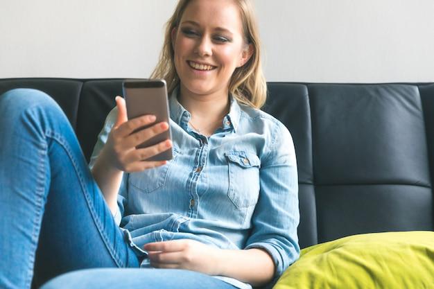 Mujer joven con el teléfono en el sofá en casa