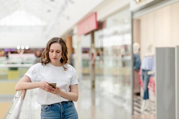 Mujer joven con el teléfono en su mano que hace el selfie.
