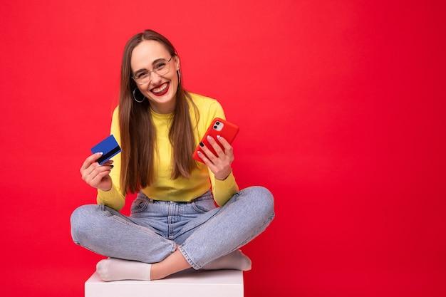 Mujer joven con teléfono y tarjeta bancaria sobre fondo rojo.