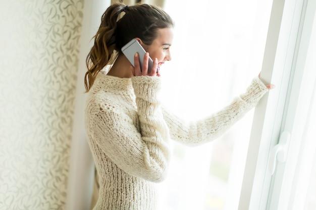 Mujer joven con telefono por ventana