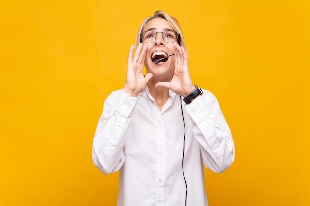 Mujer joven telemarketer que se siente feliz, emocionada y positiva, dando un gran grito con las manos al lado de la boca, gritando