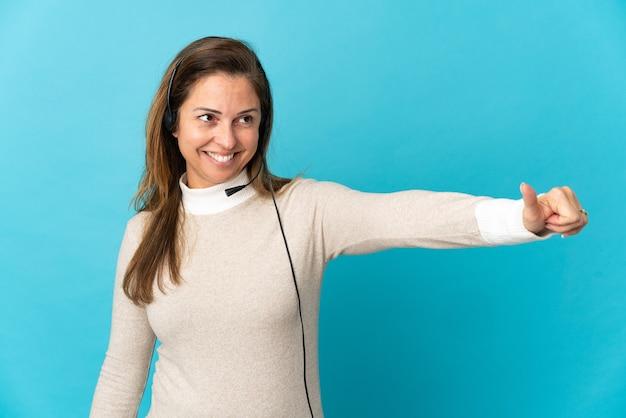 Mujer joven telemarketer sobre pared azul aislada dando un pulgar hacia arriba gesto