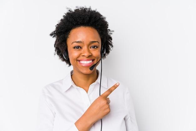 La mujer joven del teleoperador afroamericano aisló sonriendo y señalando a un lado, mostrando algo en el espacio en blanco.