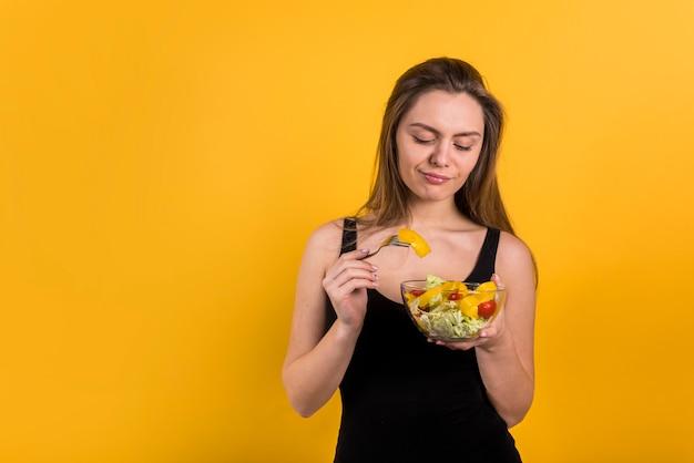 Mujer joven con tenedor y plato de ensalada