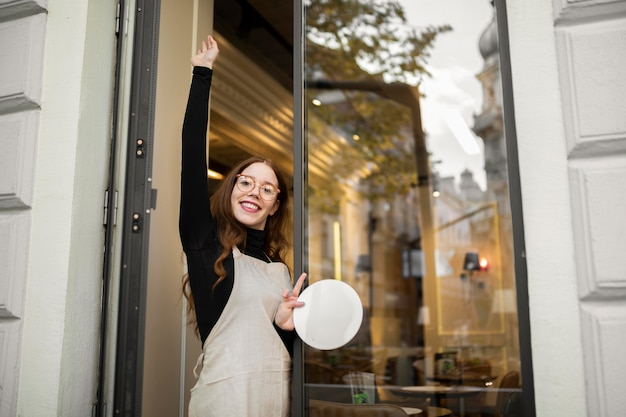 Mujer joven, tenencia, cartel de la tienda