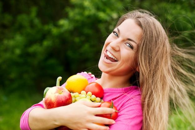 Mujer joven, tenencia, frutas y verduras Foto gratis