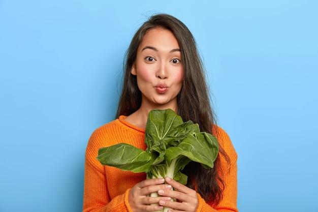 Mujer joven, tenencia, hojas verdes