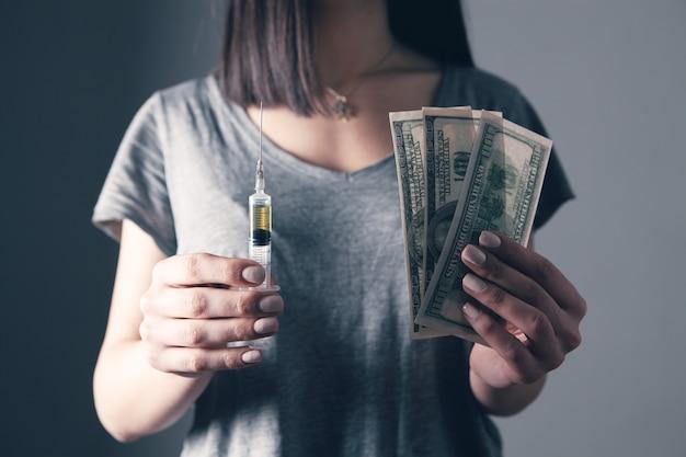 Mujer joven, tenencia, jeringa, y, dinero