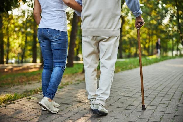Mujer joven, tenencia, mano, de, hombre mayor, en la calle