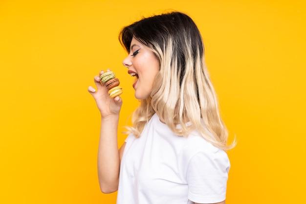 Mujer joven, tenencia, maracrons, aislado, en, fondo amarillo