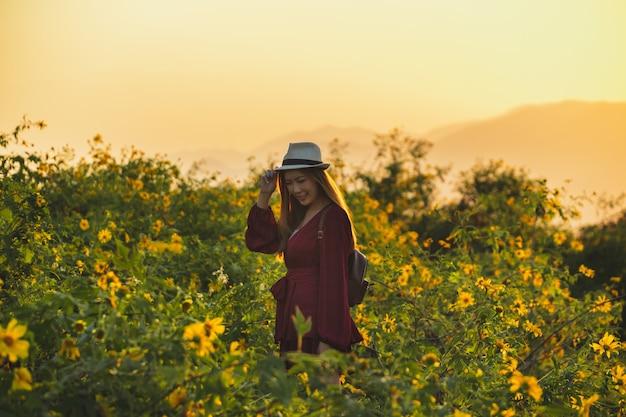 Mujer joven, tenencia, sombrero, con, ocaso